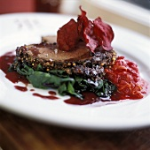 A slice of roast beef with beetroot crisps on spinach
