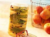 Spicy pickled apple and pepper rings in pickling jar
