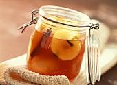 Apples in Campari and white wine in preserving jar