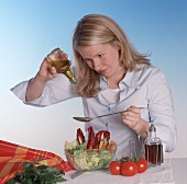 Young woman dressing mixed salad with oil
