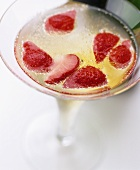 A glass of champagne with pieces of strawberry