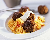 Meat balls with herb yoghurt sauce on bulgur