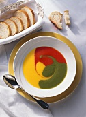 Red, yellow and green pepper soup in a plate