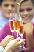 Menschen beim Anstossen mit Cocktail 'Prosecco Red'