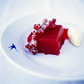 Turned-out redcurrant jelly & vanilla ice cream on plate