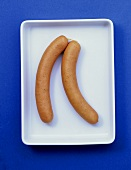 Two frankfurters in shallow bowl