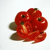 Tomatoes with drops of water, one cut into