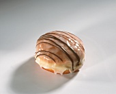 A fritter with icing and with chocolate lines