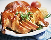 A stuffed duck with apple wedges