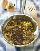 Beefsteaks with sweetcorn and onions in frying pan