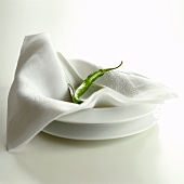 A green chili pepper on napkin and plate