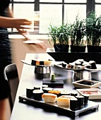 Woman at a buffet with various sushi