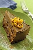 A piece of chocolate orange cake with orange zest