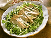 Chicken breast fillets, cut up, on vegetable salad
