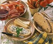 Brotzeit mit Olivenbrot mit Kräuterquark Käse und Schinken