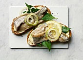 Open sandwiches with marinated herrings, mint and lemon