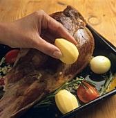 Placing vegetables round sautéed leg of lamb