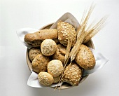Wholemeal rolls in bread basket with ears of corn