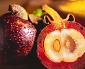 A whole and a halved mangosteen