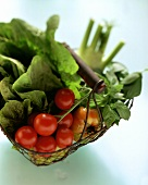 Tomatoes, salad leaves and vegetables in a basket