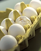 weiße Eier im Karton (ein Ei mit zerbrochener Schale)