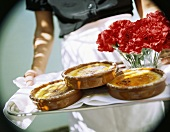 Hands holding tray with Crema catalana and carnations