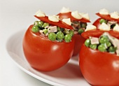 Stuffed tomatoes with cooked ham, peas and onions