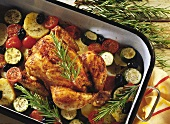 Rosemary chicken on bed of vegetables in a roasting tin