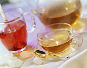 A cup of tea and a glass of fruit tea with glass teapot