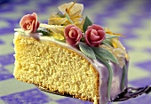 A piece of sponge cake with icing & marzipan roses