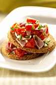 Oat cakes topped with ham and tomatoes