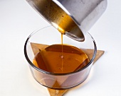 Pouring liquid caramel into a glass mould
