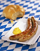 Sausages with mustard on paper plate (Bavaria, Germany)