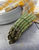 A bunch of green asparagus, plate behind