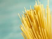 Spaghetti against turquoise background
