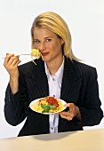 Young blond woman eating spaghetti with tomato sauce
