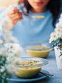 Young woman eating potato soup