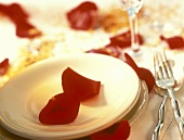 Table setting with red rose petals