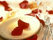 Tischgedeck mit roten Rosenblättern