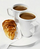 Two cups of cocoa with croissant