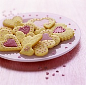 Heart-shaped biscuits with pink icing and sugar pearls
