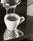 Espresso running out of espresso machine (b/w photo)
