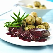 Venison fillet with red wine sauce, potatoes and beans