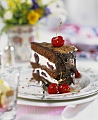 A piece of chocolate cream gateau with cherries