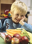 Small boy sitting at table with fruit and vegetables