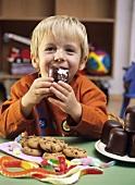 Kleiner Junge isst einen Schokokuss