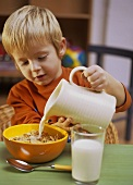 Small boy pouring milk over cornflakes