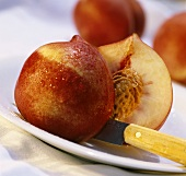Halved nectarine with knife