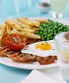Fried egg with fried ham, peas and chips