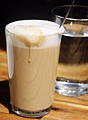 Latte macchiato, a glass of water behind